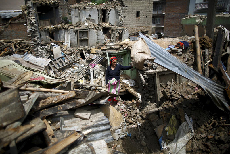 Image: A woman stands on the debris of collapsed houses after a fresh 7.3-magnitude earthquake struck Nepal, in Sankhu