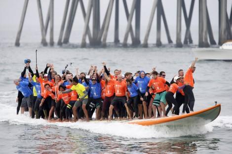 66 surfers pile onto giant board, set record