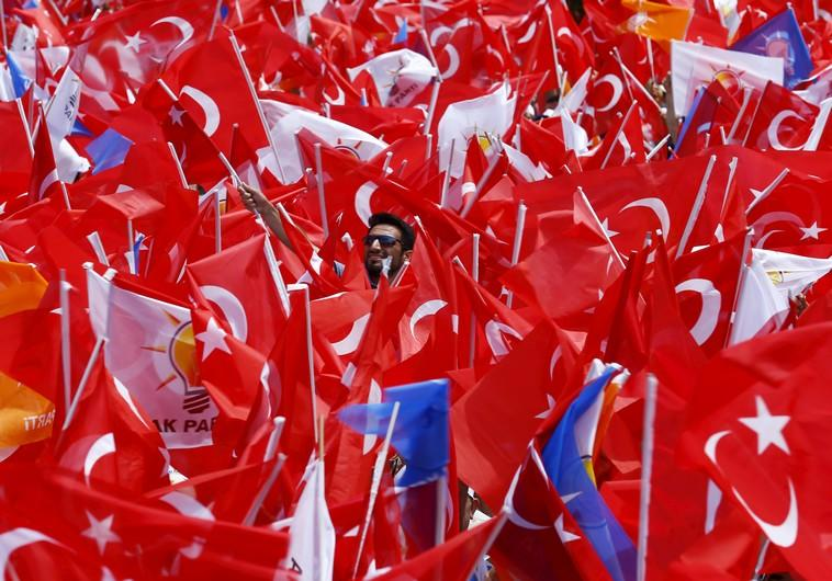 Supporters of the ruling AK Party wave Turkish national and party flags as they listen to Turkish Prime Minister Ahmet Davutoglu (not pictured) during an election rally for Turkey's June 7 parliamentary election, in Antalya, Turkey, June 6, 2015. REUTERS/Umit Bektas       TPX IMAGES OF THE DAY      - RTX1FDRF