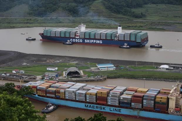 The COSCO Shipping Panama cargo ship, top, heads towards the new Cocoli locks, part of the new Panama Canal expansion project, as it cruises past another cargo ship passing through the old Pedro Miguel locks, in Panama City, Sunday, June 26, 2016. Authorities are hosting a big bash to inaugurate newly expanded locks that will double the Canal's capacity, as the country makes a multibillion-dollar bet on a bright economic future despite tough times for international shipping. (AP Photo/Dario Lopez-Mills)