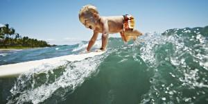 Toddler riding wave on surfboard smiling
