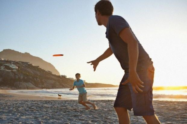Father with son (7-9) playing frisbee on beach --- Image by © Felix Wirth/Corbis