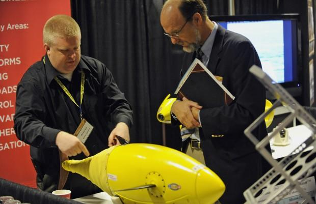 101109-N-7676W-172  ARLINGTON, Va. (Nov. 9, 2010) Michael Rufo, left, with Boston Engineering, explains the BIOSwimmer, a flexible hulled autonomous underwater vehicle, designed for high maneuverability in harsh environments, during day two of the Office of Naval Research 2010 Naval Science and Technology Partnership Conference. (U.S. Navy photo by John F. Williams/Released)