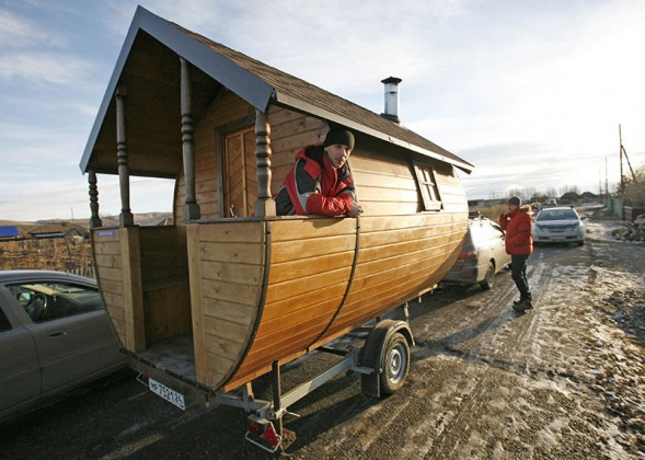 Valentine Krasin stands on his home-made mobile wooden Russian banya as he waits for friends in the village of Shoshino, about 455 km southeast of Russia's Siberian city of Krasnoyarsk, December 1, 2013. Krasin designed and constructed the mobile bathing station based on a traditional Russian banya or steam bath, intending it for trips with friends and possibly as a small commercial venture. Picture taken December 1, 2013.  REUTERS/Ilya Naymushin (RUSSIA - Tags: SOCIETY HEALTH) - RTX160UP